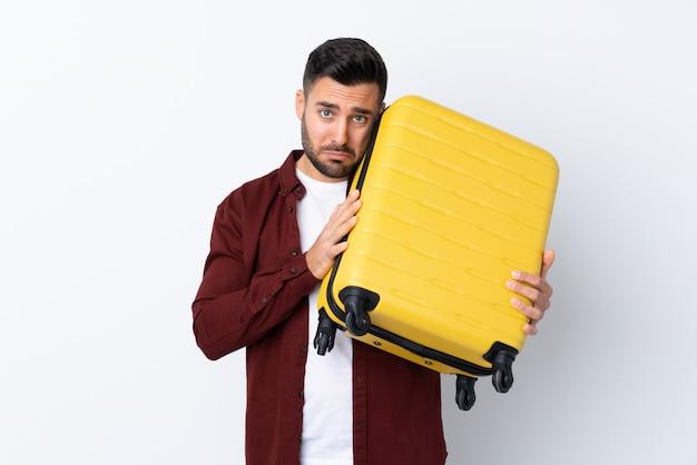 Jeune Bel Homme Sur Un Mur Blanc Isolé En Vacances Avec Valise De Voyage Et Malheureux Photo Premium