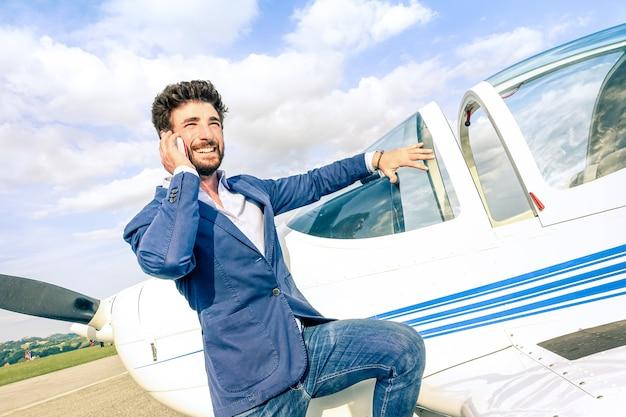 Jeune bel homme parlant avec un téléphone mobile intelligent à l'avion privé Photo Premium