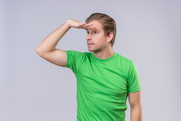 Jeune Bel Homme Portant Un T-shirt Vert à La Recherche De Loin Photo gratuit