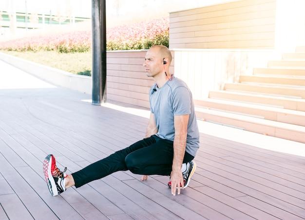 Jeune bel homme qui s'étend d'exercice dans le parc Photo gratuit