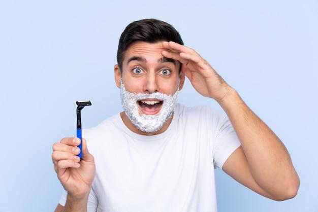 Jeune Bel Homme Rasant Sa Barbe Avec Surprise Et Expression Faciale Choquée Photo Premium