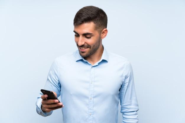Jeune bel homme avec son portable sur un mur bleu isolé, souriant beaucoup Photo Premium