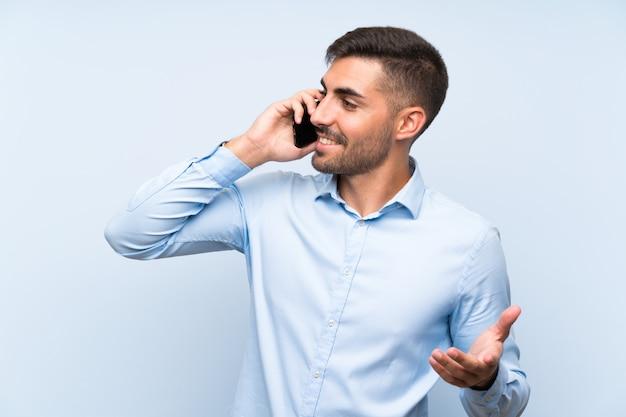Jeune bel homme avec son téléphone portable sur un mur bleu isolé Photo Premium