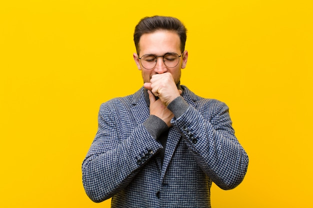 Jeune bel homme souffrant de maux de gorge et de grippe, toussant avec la bouche couverte Photo Premium