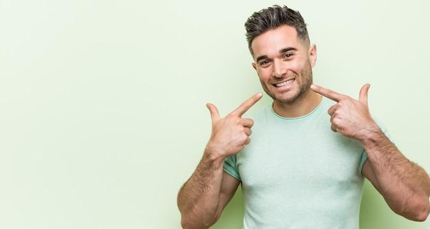 Jeune bel homme sourit, pointant les doigts sur la bouche. Photo Premium