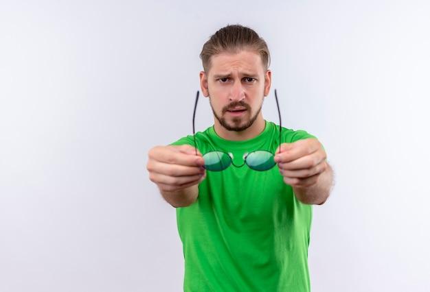 Jeune Bel Homme En T-shirt Vert Regardant La Caméra Avec Une Expression Confiante Qui S'étend Des Lunettes Debout Sur Fond Blanc Photo gratuit