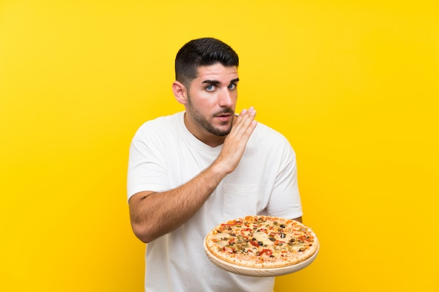 Jeune bel homme tenant une pizza sur un mur jaune isolé murmurant quelque chose Photo Premium