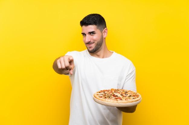 Jeune bel homme tenant une pizza sur un mur jaune isolé pointe le doigt vers vous avec une expression confiante Photo Premium