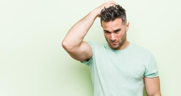 Jeune bel homme sur vert fatigué et très somnolent en gardant la main sur la tête. Photo Premium