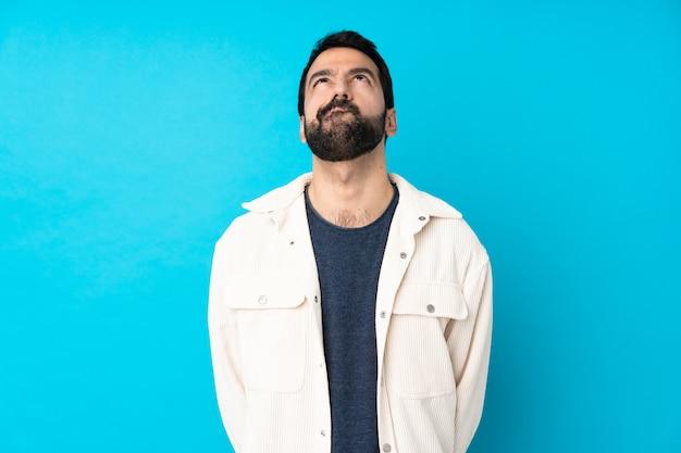 Jeune Bel Homme Avec Veste En Velours Côtelé Blanc Sur Mur Bleu Isolé Et Levant Photo Premium