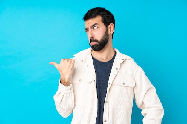 Jeune Bel Homme Avec Veste En Velours Côtelé Blanc Sur Mur Bleu Isolé Malheureux Et Pointant Vers Le Côté Photo Premium