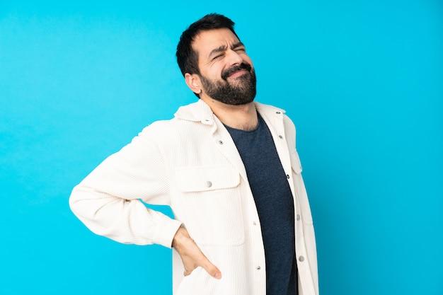 Jeune Bel Homme Avec Veste En Velours Côtelé Blanc Sur Mur Bleu Isolé Souffrant De Maux De Dos Pour Avoir Fait Un Effort Photo Premium