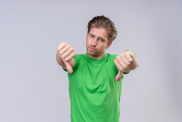 Jeune Bel Homme Vêtu D'un T-shirt Vert Malheureux Montrant Les Pouces Vers Le Bas Debout Sur Un Mur Blanc Photo gratuit