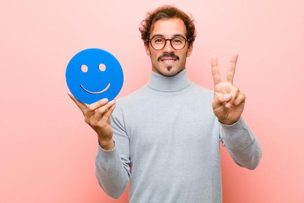 Jeune bel homme avec un visage souriant contre le mur plat rose Photo Premium