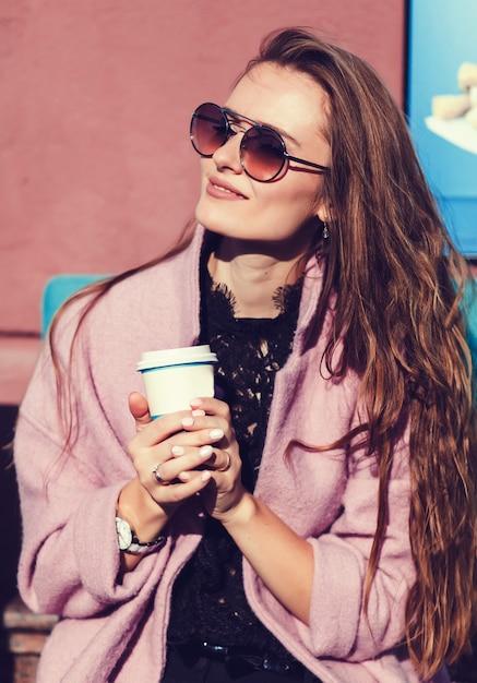 Jeune belle brune avec un café en ville Photo Premium