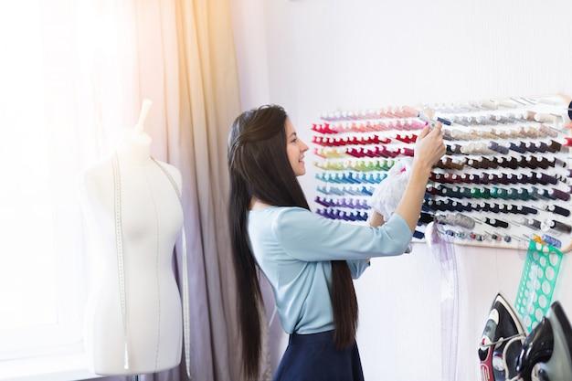 Jeune belle couturière à la recherche de fils pour tissus sur son lieu de travail. Photo Premium