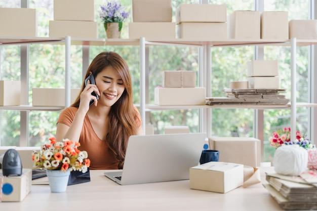 Jeune belle femme d'affaires asiatique heureuse en tenue décontractée avec visage souriant appelle pour recevoir les commandes du client avec un ordinateur portable à son bureau à domicile de démarrage, concept pme Photo Premium