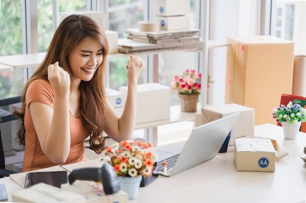 Jeune belle femme d'affaires asiatique heureuse avec visage souriant utilise un ordinateur portable avec des offres commerciales de succès, excitée par les bonnes nouvelles, femme assise, levant la main dans un geste oui célébrant le succès de l'entreprise Photo Premium