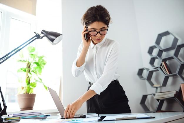 Jeune Belle Femme D'affaires Confiant Parlant Au Téléphone Au Lieu De Travail Au Bureau. Photo gratuit