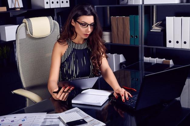 Jeune belle femme d'affaires travaillant au bureau noir élégant Photo Premium