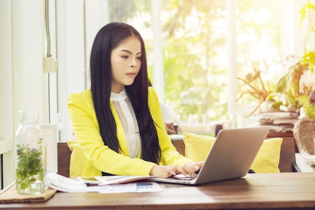 Jeune belle femme asiatique assise à table dans un café travaillant avec un ordinateur portable Photo Premium
