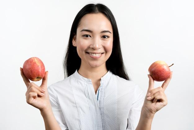 Jeune belle femme asiatique montrant deux pommes rouges en face de fond blanc Photo gratuit
