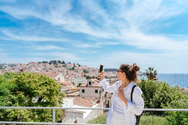 Jeune belle femme sur un balcon surplombant une petite ville de croatie Photo gratuit