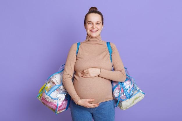 Jeune Belle Femme Enceinte Debout Isolée Sur Mur Lilas, Toucher Son Ventre, Tenant Des Sacs Avec Des Trucs Pour La Maison De Maternité. Photo gratuit