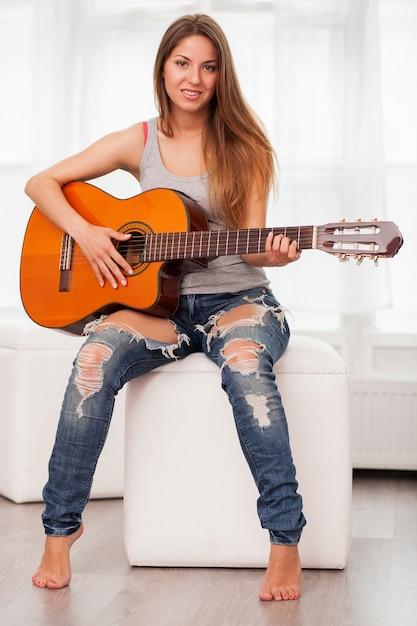 Jeune belle femme jouant de la guitare Photo gratuit