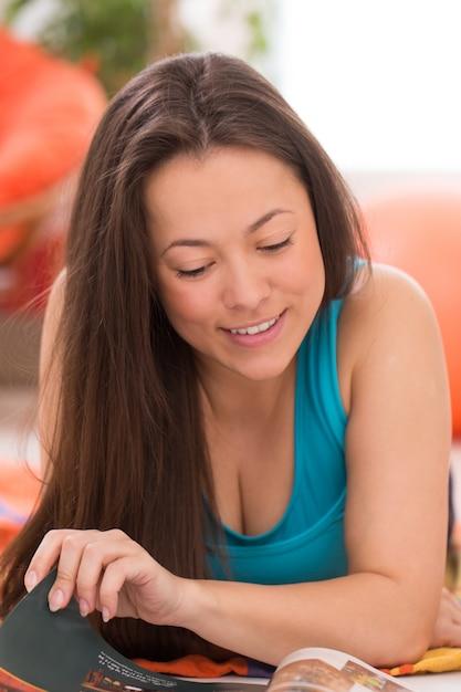 Jeune belle femme lisant à la maison Photo gratuit