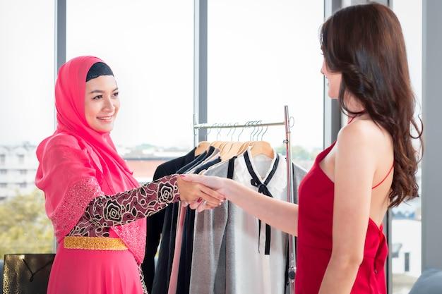 Jeune belle femme musulmane serrant la main avec des amitiés caucasiennes, assis près de sacs à provisions et tablette bénéficiant en shopping au café. Photo Premium