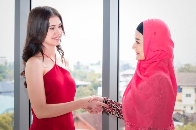 Jeune belle femme musulmane, serrant la main avec des amitiés caucasiennes. Photo Premium