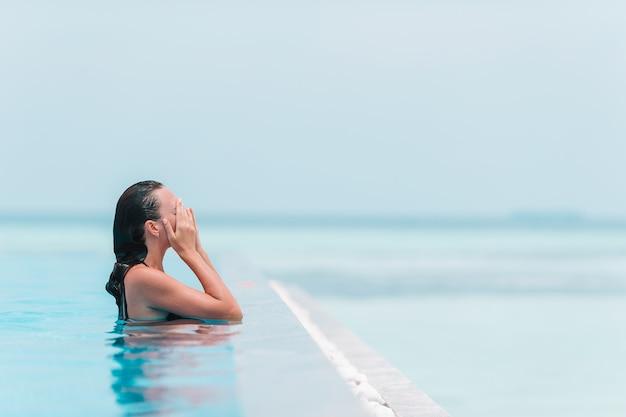 Jeune belle femme profitant de la piscine calme et luxueuse Photo Premium