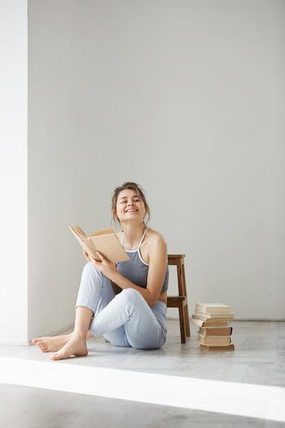 Jeune Belle Femme Tendre Souriant Tenant Un Livre Assis Sur Le Sol Sur Un Mur Blanc Tôt Le Matin. Photo gratuit