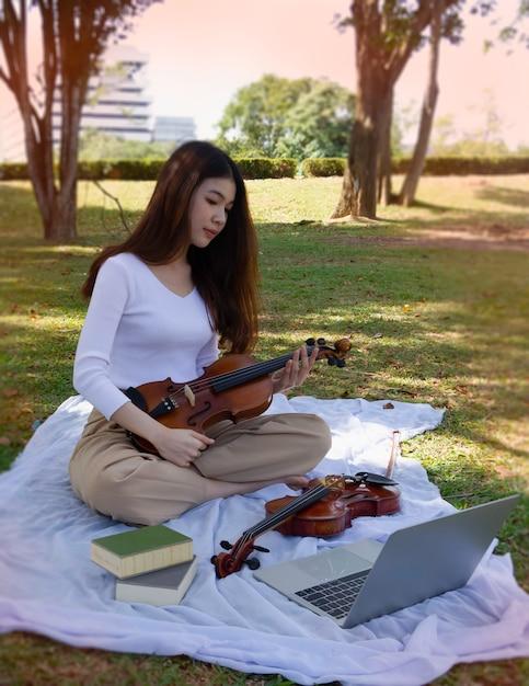 Jeune Belle Femme Tient Le Violon à La Main, à La Recherche D'un Ordinateur Portable, Apprenant à Jouer D'un Instrument Acoustique. Photo Premium