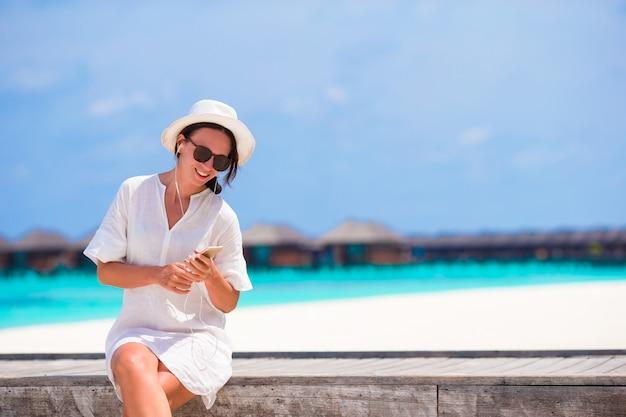 Jeune belle fille au pont de bois écouter de la musique par son téléphone Photo Premium