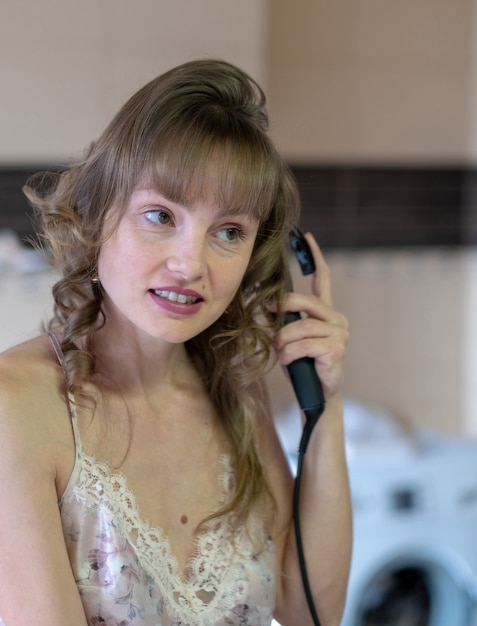 Jeune belle fille aux cheveux blonds fait friser les cheveux Photo Premium
