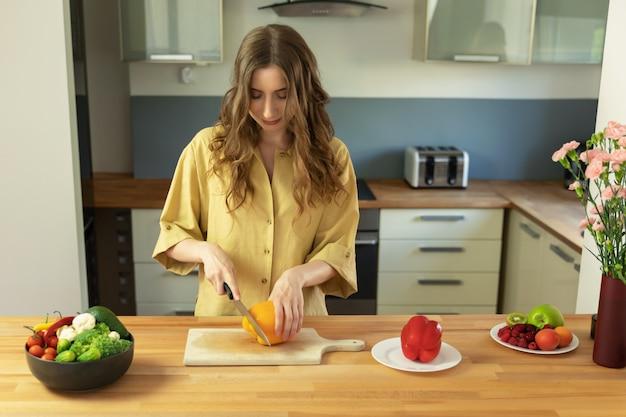 Jeune belle fille aux cheveux longs tranches de poivron. une femme prépare une salade de légumes frais et sains. Photo Premium