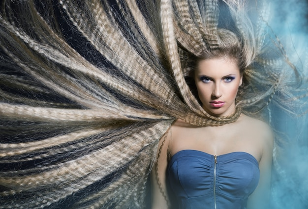 Jeune Belle Fille Aux Longs Cheveux Ondulés Agitant Dans La Fumée Est Dans Le Bleu Fone.portret. Photo Premium