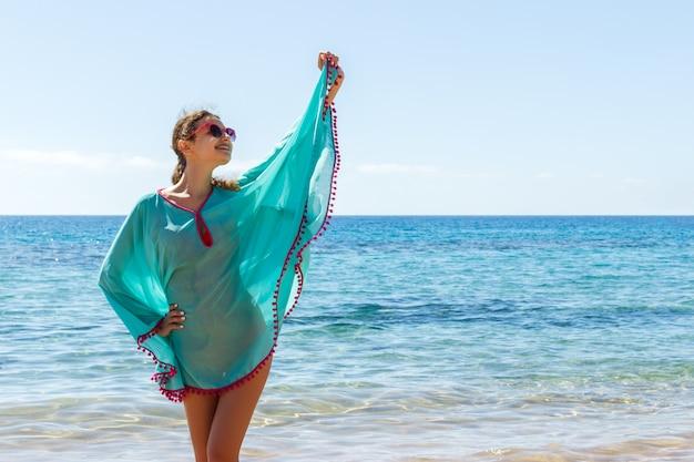 Jeune belle fille blonde à lunettes s'amuser sur la plage Photo Premium