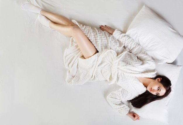Jeune belle fille brune en peignoir allongé sur le lit tôt le matin. tiré d'en haut Photo Premium