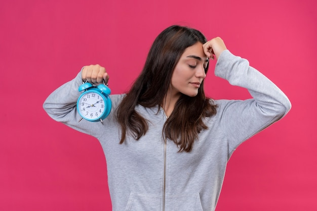 Jeune Belle Fille à Capuche Gris à La Recherche De Suite Avec La Main Sur Le Front Pensant Tenant Horloge Debout Sur Fond Rose Photo gratuit