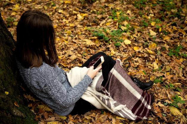 Jeune belle fille dans une veste grise assis dans la forêt en automne près d'un grand arbre avec un téléphone portable Photo Premium