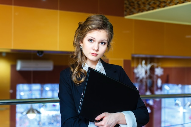 Jeune belle fille debout dans un bureau et tenant un ordinateur portable Photo Premium
