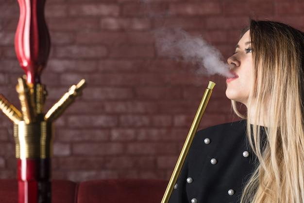 Jeune et belle fille fume un narguilé Photo Premium