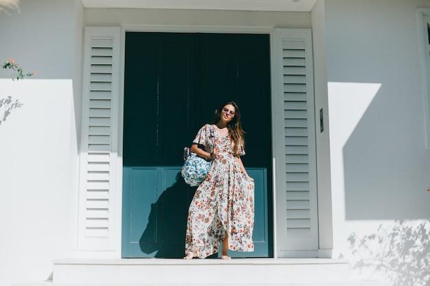 Jeune belle fille posant dans la rue dans une robe avec un sac à dos Photo gratuit