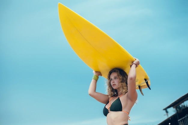 Jeune belle fille posant sur la plage avec une planche de surf, surfeuse, vagues de l'océan Photo gratuit