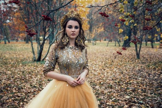 Jeune belle fille sexy en robe d'or dans la forêt d'automne Photo Premium