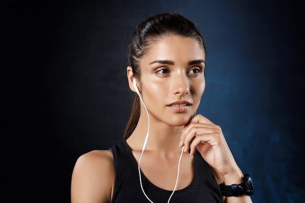 Jeune Belle Fille Sportive écoute De La Musique Sur Un Mur Sombre. Photo gratuit