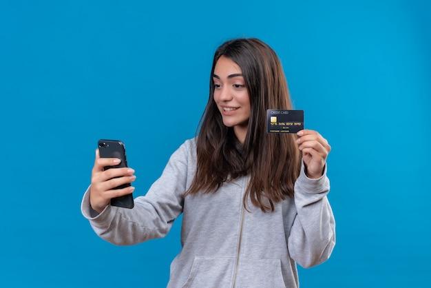 Jeune Belle Fille En Sweat à Capuche Gris Tenant Le Téléphone Et Montrer La Carte De Crédit Au Téléphone Est Venu Avec Le Sourire Sur Le Visage Debout Sur Fond Bleu Photo gratuit